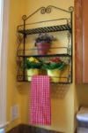Potted flowers and kitchen towel on a hanging rack with shelves